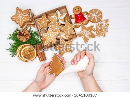 Woman hands paint ornaments on Xmas treats. Christmas preparations. Hands decorate handmade Christmas gingerbread with glaze, icing sugar. Female hands paint Christmas gingerbread cookies. Top view