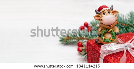 Toy bull in a Santa Claus hat on a red gift box on a white wooden background.Christmas tree branch with red berries in the background. Bull as a symbol of the New year 2021.New Year,Christmas concept
