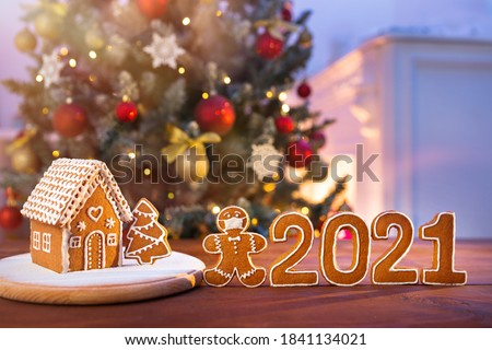 Homemade gingerbread house on the background of a decorated Christmas tree and unfocused lights with a masked man cookies, and numbers of new year #1841134021