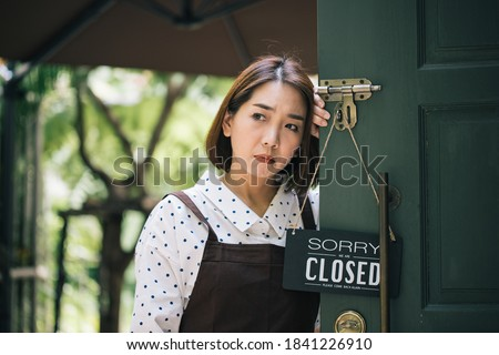 Asian beautiful woman sad mood with closed sign board hanging on the door of cafe because due to viral infection. Coronavirus and quarantine concept. go out of business