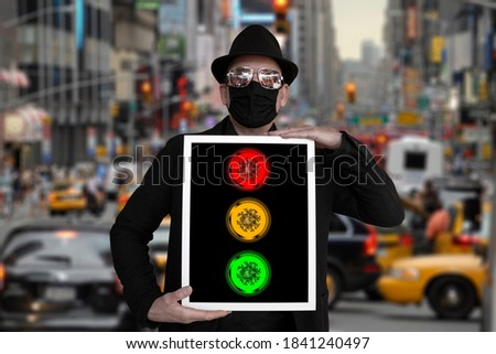 A man stands on a street and holds a picture in which a traffic light can be seen