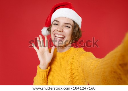 Close up of funny young Santa woman in sweater Christmas hat doing selfie shot on mobile phone waving greeting with hand isolated on red background. Happy New Year celebration merry holiday concept