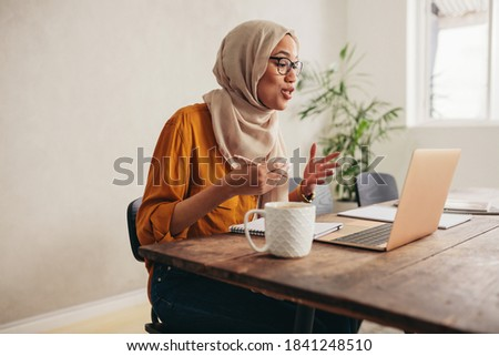 Muslim businesswoman working at home due to pandemic isolation. Female wearing hijab talking over a video call with team. Royalty-Free Stock Photo #1841248510