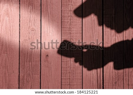 Detective Silhouette with a searchlight on Grungy Wooden Background. #184125221