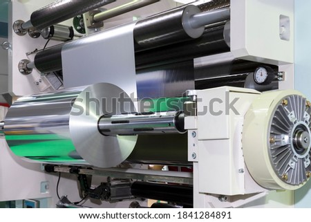 roll of aluminum foil for food packaging on automatic packing machine in food product factory. industrial and technology concept.  Royalty-Free Stock Photo #1841284891