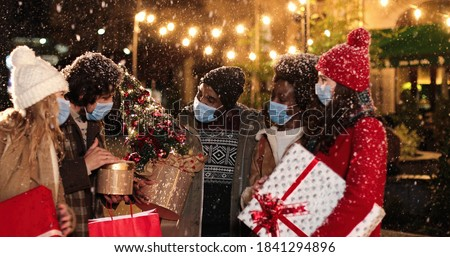 Portrait of happy multi-ethnic people with christmas presents talking while standing in city while snowing. Caucasian and African American families with gifts. Little kids in good mood. Winter concept