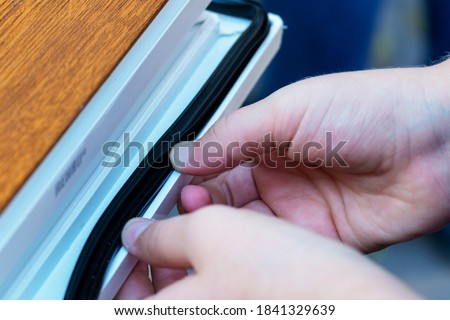 Hands applying rubber strip. Concept improvement of sealing, sound insulation, thermal insulation of windows and doors. Professional sealing a window frame. Rubber insulation  in a plastic window. #1841329639