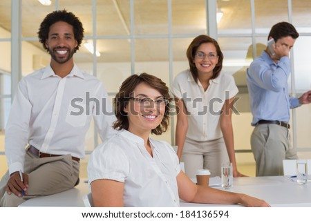 Portrait of a smiling young businesswoman with colleagues in background at office #184136594