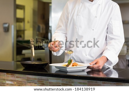 Closeup mid section of a chef garnishing food in the kitchen #184138919