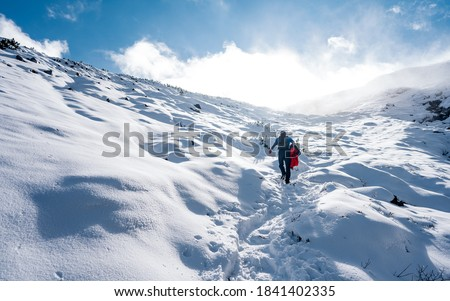 Hiker ascent to the summit. Winter ice and snow climbing in mountains. A success of mountaineer reaching the summit. Outdoor adventure sports in winter alpine moutain landscape. #1841402335