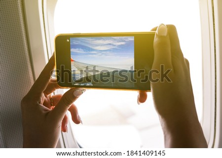 The passenger takes pictures on the plane. Girl makes a photo from the window of the airliner on a mobile phone camera. Close-up of hands and smartphone screen. Travel and technology