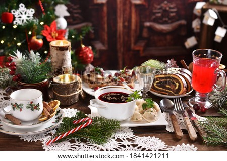 traditional in Poland Christmas Eve dishes with red borscht and dumplings, herring with cranberries and poppy seed roll cake on festive table in rustic style #1841421211