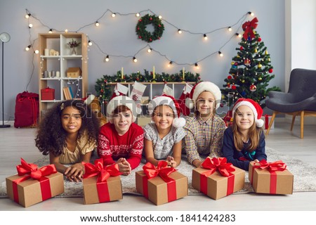 Portrait of a group of happy smiling diverse children lying on the floor near Christmas presents tied with beautiful red bows and looking at camera. Children pose in a room with Christmas decorations. #1841424283
