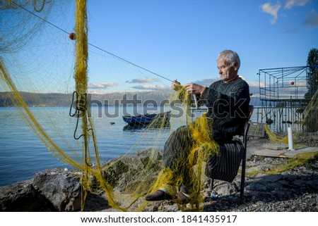 Senior fisherman holding fishing net near the beach. Fisherman hands close up. A fisherman preparing the fishing net Royalty-Free Stock Photo #1841435917