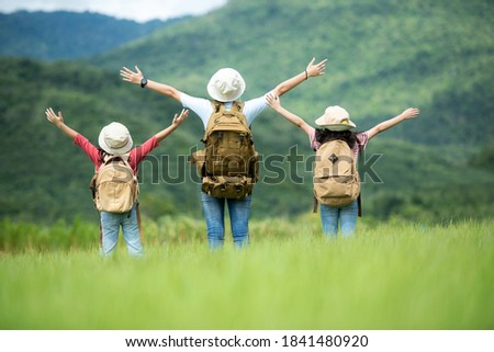 Group family children travel nature trips raise arms and standing see mountain outdoors, adventure and tourism for destination leisure trips for education and relax in nature park. Travel vacations  Royalty-Free Stock Photo #1841480920