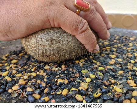 uttarakhand, india-3 june 2020:ancient method of grinding.this is a picture of a stone grinder grinding seeds. this picture shows a round stone over a flat one.