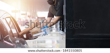 Drive through and takeaway for buy fast food for protect covid19. New normal life style. The staff woman wearing medical glove and mask and handed a food to customer. Drive thru and take away concept. Royalty-Free Stock Photo #1841550805