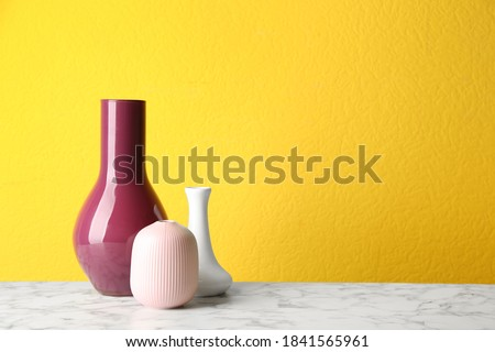Stylish ceramic vases on white marble table against yellow background. Space for text Royalty-Free Stock Photo #1841565961
