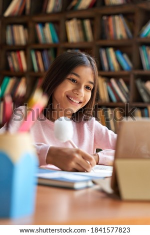 Happy indian latin girl school pupil distance learning online at virtual class with teacher tutor by video conference call, watching tv lesson on digital tablet computer at home, in classroom. Royalty-Free Stock Photo #1841577823