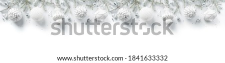 Merry Christmas wreath made of fir branches, white and silver decorations, sparkles and confetti on white background. Xmas and New Year holiday, bokeh, light. Flat lay, top view, wide banner Royalty-Free Stock Photo #1841633332