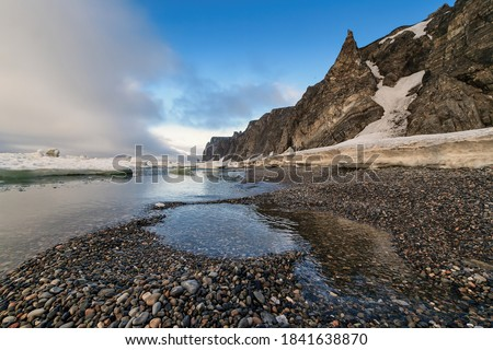 Coast of the Arctic Ocean near the Bering Strait. Cold summer in the Arctic. Melting ice at the end of June on the coast of the Arctic Ocean. Cape Uelen, Chukchi Peninsula, Chukotka, Far East Russia. #1841638870