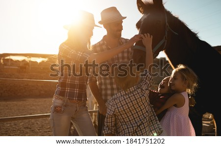 Happy family with horse having fun at farm ranch - Parentc and children cuddling animal pet at sunset outdoor - Love and youth concept - Soft focus on father face Royalty-Free Stock Photo #1841751202
