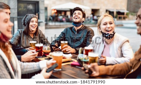Young friends drinking beer wearing face mask - New normal lifestyle concept with people having fun together talking on happy hour at outside brewery bar - Bright warm filter with focus on central guy Royalty-Free Stock Photo #1841791990