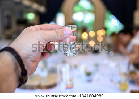 Wedding or party concept. Hand with a glass of vodka guest makes a toast, raising a glass Royalty-Free Stock Photo #1841804989