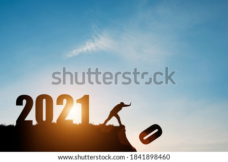 Man push number zero down the cliff where has the number 2021 with blue sky and sunrise. It is symbol of starting and welcome happy new year 2021. #1841898460