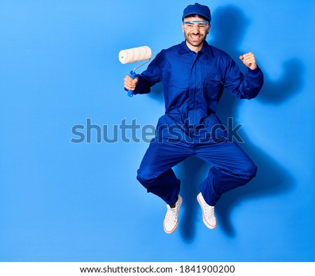 Young handsome hispanic man wearing painter uniform and cap smiling happy. Jumping with smile on face holding roller doing winner sign with fists up over isolated blue background