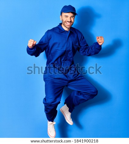 Young handsome hispanic man wearing painter uniform and cap smiling happy. Jumping with smile on face doig winner sign with fists up over isolated blue background