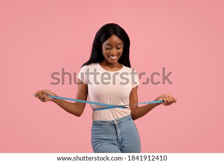Weight loss and healthy lifestyle concept. Slim black woman measuring her waist with tape over pink studio background. Fit African American lady in perfect shape, happy with her body Royalty-Free Stock Photo #1841912410
