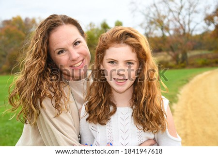 Mother and daughter take fall portrait picture.