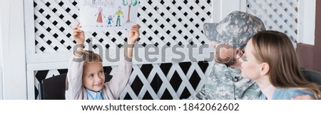 Happy girl showing picture with family near mother and father at home, banner