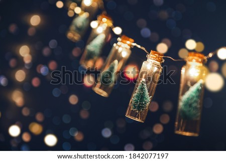 Close-up, Elegant Christmas tree in glass jar with bokeh lights background, copy space. Christmas and new year concept. Royalty-Free Stock Photo #1842077197