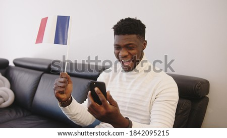 Young black man watching game play on smartphone and waving flag of France. High quality photo