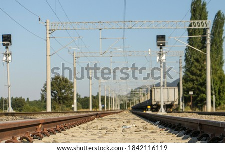 The focal point of the photograph is the ground and stones between the train tracks. This is a picture of a railroad transport line.  The railway and the electrical wires around it attract attention.
