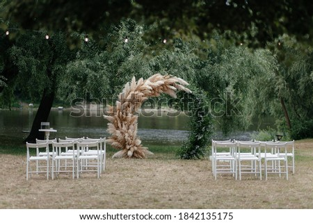 Wedding arch under the tree and chairs for guests. Outside ceremony place. Wedding arch. Wedding ceremony place Royalty-Free Stock Photo #1842135175