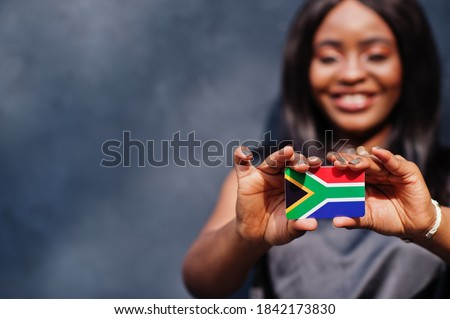 African woman hold small South Africa flag in hands. Royalty-Free Stock Photo #1842173830