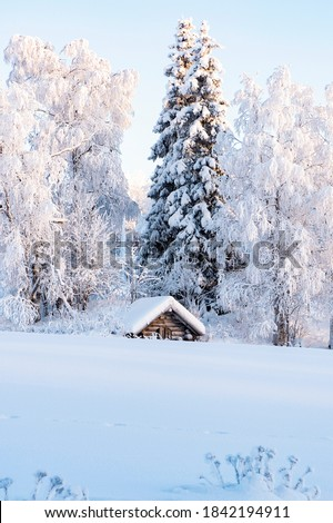 Snowy winter landscape of Lapland. Wooden, village houses covered with thick snow. Royalty-Free Stock Photo #1842194911