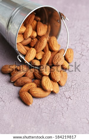 Almonds in bucket on color wooden background #184219817