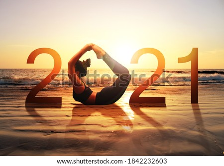 Happy new year card 2021. Silhouette of healthy girl doing Yoga Bow pose on tropical beach with sunset sky background, woman practicing yoga as a part of the Number 2021 sign. #1842232603