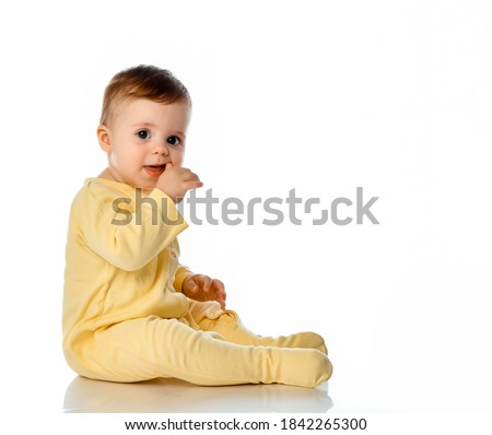 Little baby girl wearing yellowe jumpsuit scratching first teeth growing in gum with hand finger sitting on floor studio shot. Full length portrait isolated on white copy space. Teething concept Royalty-Free Stock Photo #1842265300