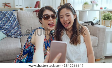 two beautiful young asian japanese sisters taking self picture on cellphone with grimacing and putting tongue out.
