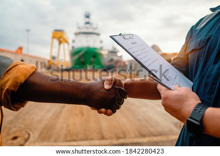 marine contractor businessman handshaking with worker on the ship with contract agreement. Handshake of two boilersuits with different colors wiyh maritime background Royalty-Free Stock Photo #1842280423