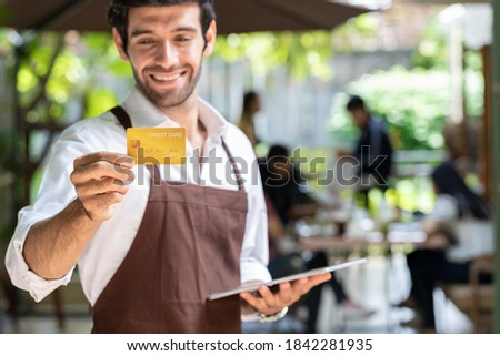 Young handsome businessman owns a coffee shop, holding a tablet and a credit card to tell customers to cash pay for the all service. Small business ideas, start up.