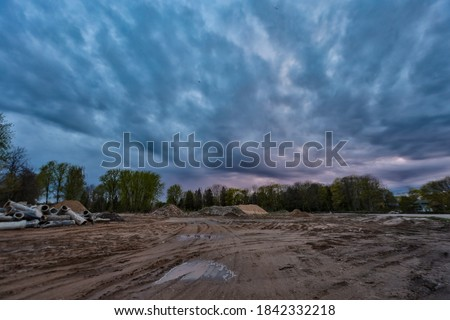 Cloudy industrial view of construction site with sand. Photo taken in atvia, abandoned lot.