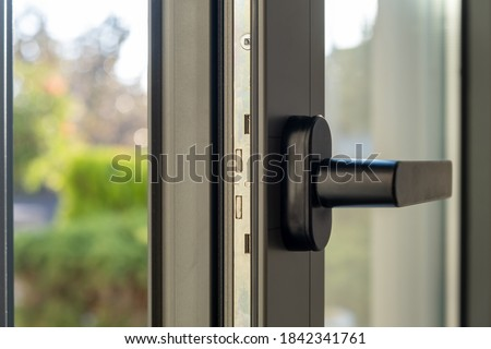 Aluminum window detail. Metal door frame open closeup view. Energy efficient, safety profile, blur green outdoor background Royalty-Free Stock Photo #1842341761