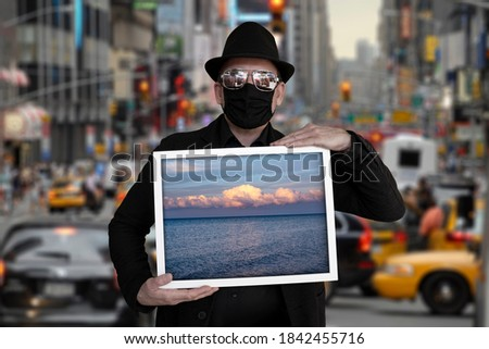 A man stands on a street and holds a picture in which the sea can be seen