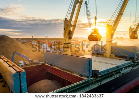 Large international transportation vessel in the port, loading grain during sunrise for export in the sea waters. Royalty-Free Stock Photo #1842483637